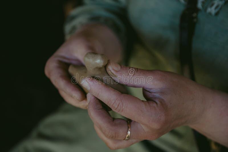 Garncarka pracuje z gliną, ugniata glinę i zwilża, rzemieślnik ręk zamknięty up, fotografia stock