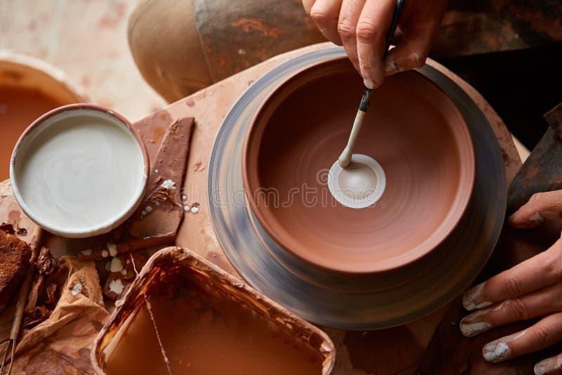 Garncarka przygotowywa farby farbować glina talerza w bielu w warsztatowym, odgórnym widoku, zakończenie, selekcyjna ostrość zdjęcie stock