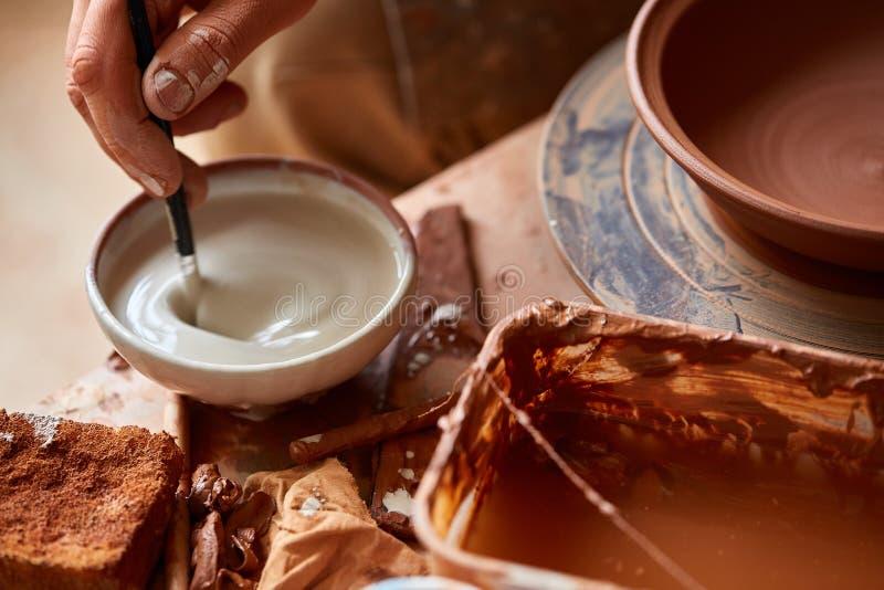 Garncarka przygotowywa farby farbować glina talerza w bielu w warsztatowym, odgórnym widoku, zakończenie, selekcyjna ostrość obraz royalty free