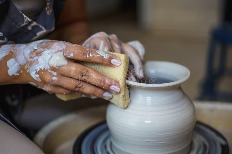 Garncarka robi ceramicznemu garnkowi lub wazie na ceramicznym kole zdjęcia royalty free
