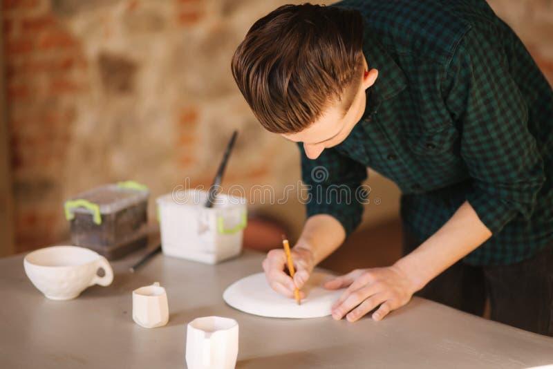 Garncarka robi ornamentowi na ceramicznym talerzu Fachowy męski garncarka remis ołówek na ceramicznym produkcie fotografia stock