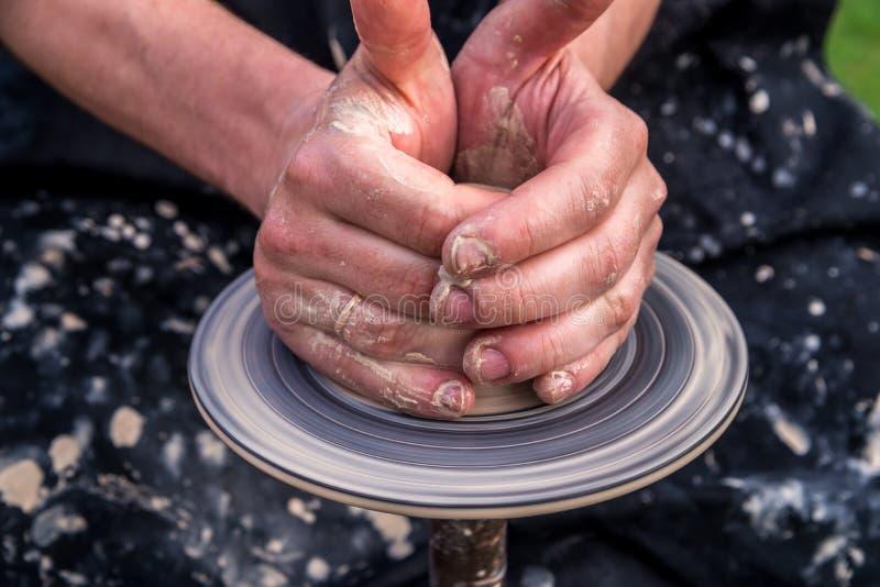 garncarstwo Men& x27; s ręki robią glinianemu garnkowi lub dzbankowi na maszynie Mężczyzna w opatrunkowej todze, spattered z glin obraz stock