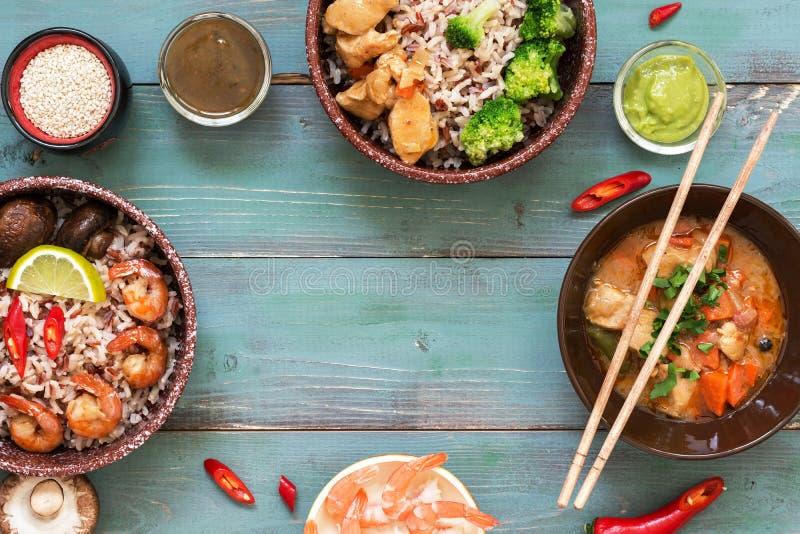 Garnela z ryż, kumberlandami, kurczakiem i pieczarkami na błękitnym drewnianym tle, Rama od Azjatyckich naczyń Odgórny widok, kop zdjęcia royalty free