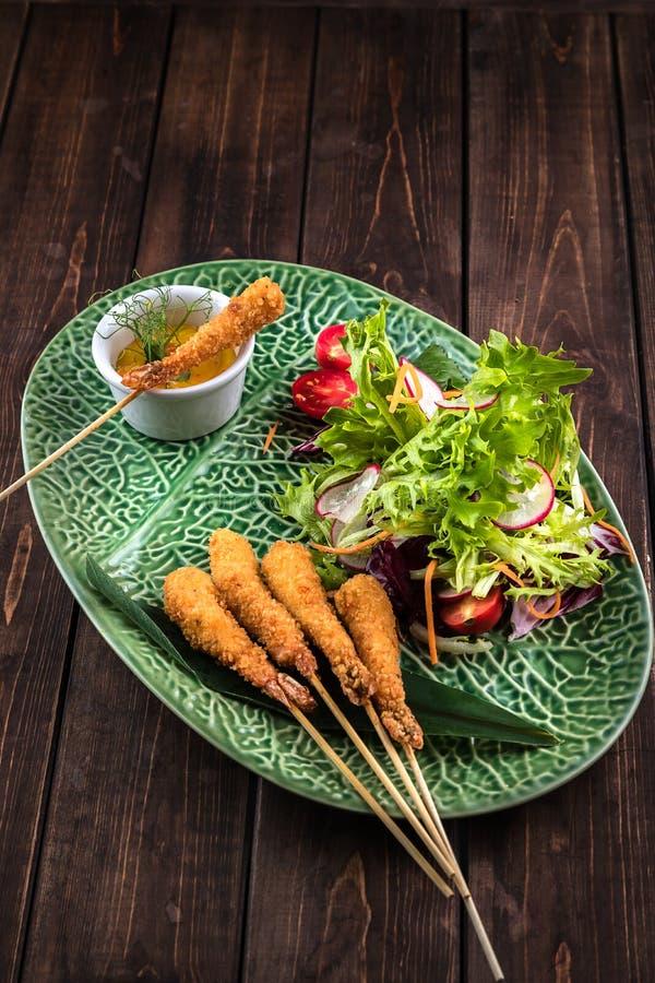Garnelen Tempura mit frischem Salat auf der grünen Platte mit einem Muster H?lzerner brauner Hintergrund Traditionelle japanische lizenzfreie stockbilder