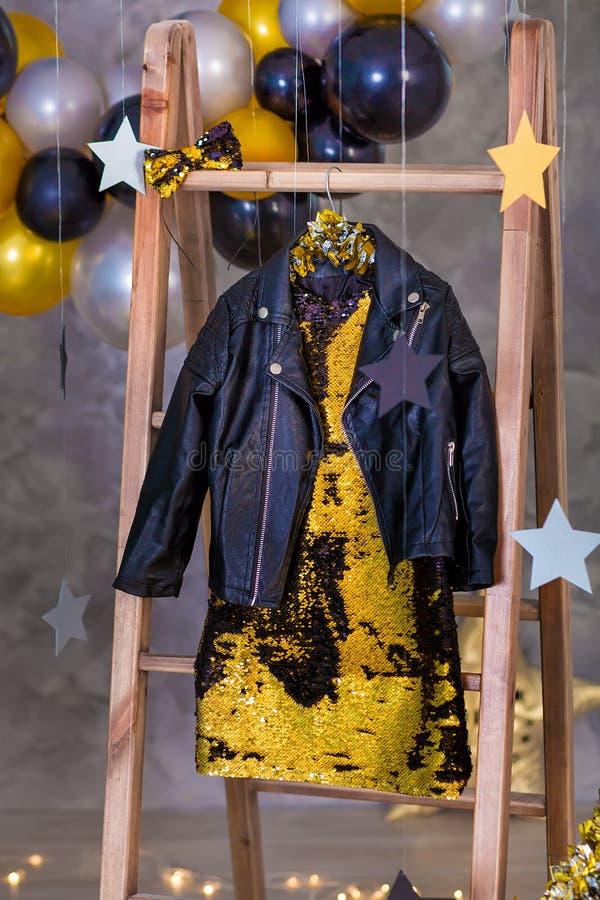Garnering av den guld- partiklänningen med läderomslaget som hänger på trähängare i klubbastudiogarneringar royaltyfri fotografi