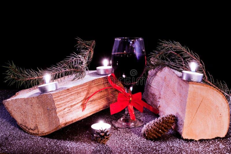 Garnering för nytt år med journaler, stearinljus, klubban, pinecones och snö på träskrivbordet arkivbild
