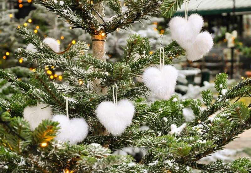 Garnering för ovanlig idérik romantisk jul eller för nytt år - vita fluffiga leksaker för hjärtaformjul på gran i vinter arkivfoton