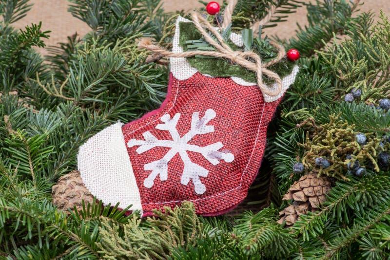 Garnering för vinterferie: snöflingavirkningjulstrumpa i mitt av en höjdpunkt för krans för tabell för Fraser gran med kottar royaltyfri foto