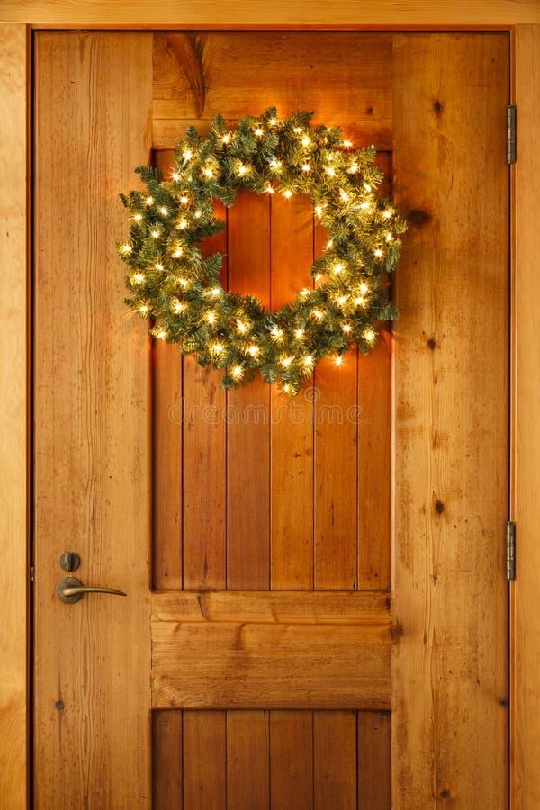 Garneringar för julkranshem med ljus som hänger på ytterdörr arkivfoton