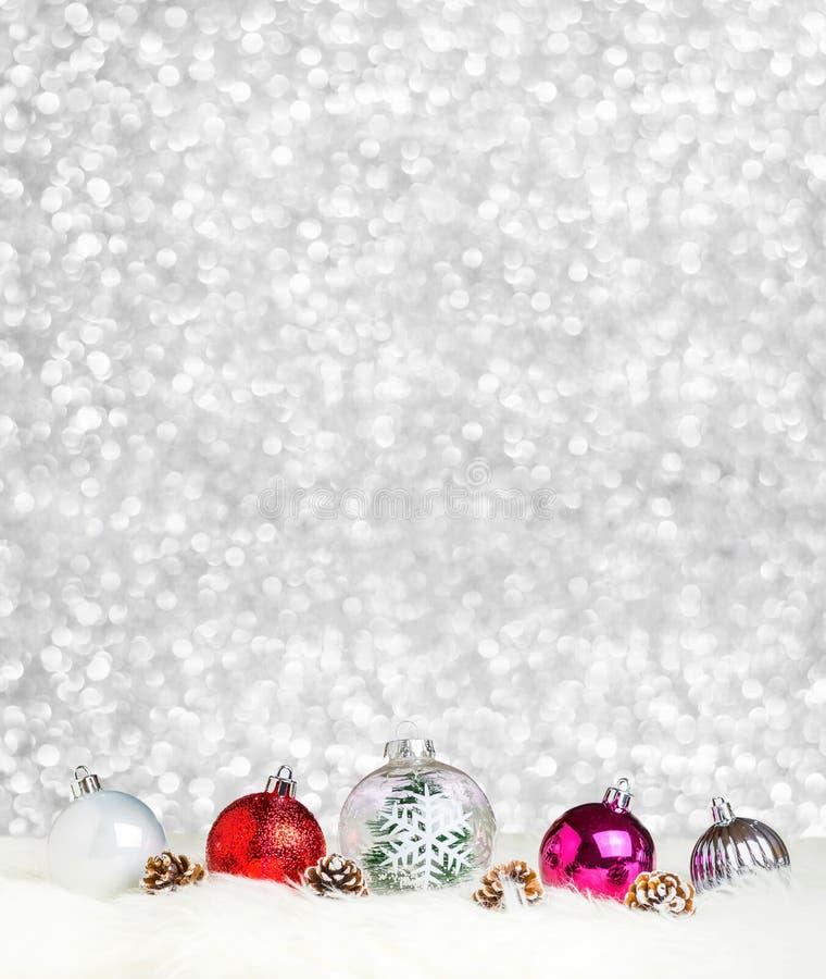 Garneringboll för glad jul på vit päls på bakgrund för silverbokehljus, för feriehälsning för baner vertikalt kort arkivfoto