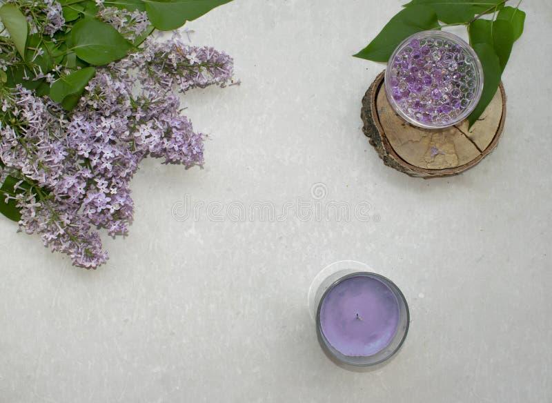 Garneringlägenheten lägger med en bukettblommalila Bollar för för Spa lavendelstearinljus och hydrogel på träskiva på grå bakgrun arkivbilder