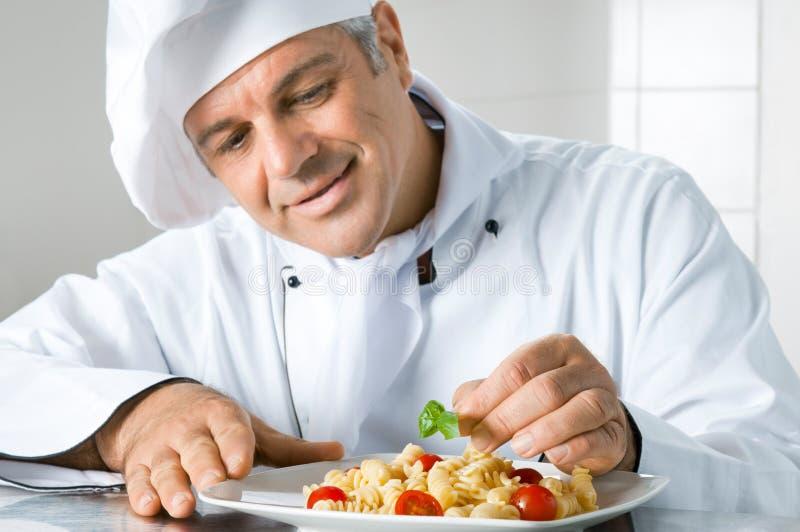 Garnish a gourmet dish. Smiling mature chef preparing an Italian dish of pasta with satisfaction stock image