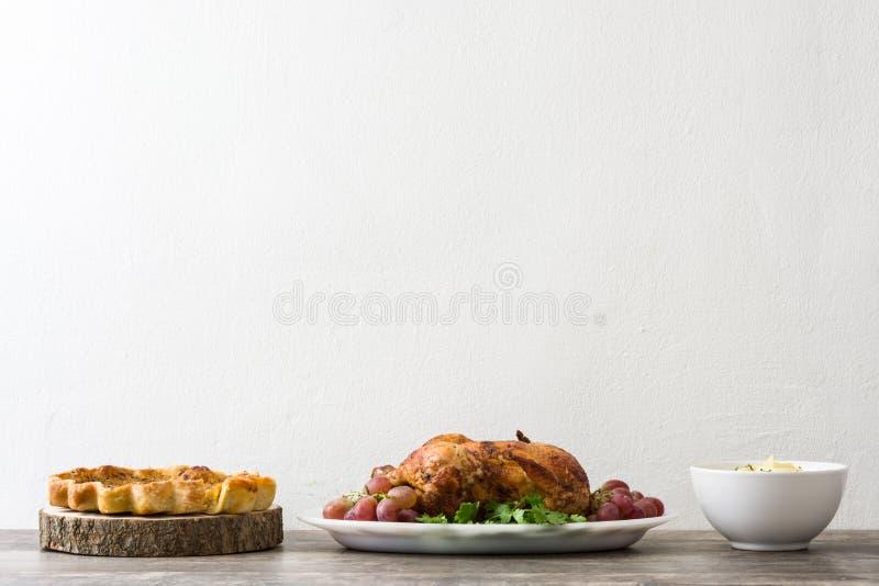 Garnished asó el pavo con las uvas y las hierbas, pastel de calabaza y puré de patata en una tabla de madera imagenes de archivo