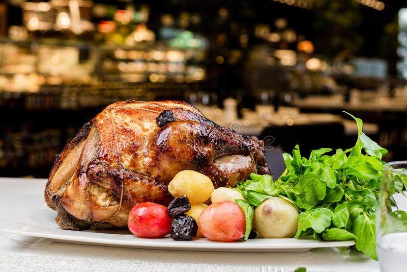 Garnished roasted turkey on platter on marble surface stock images