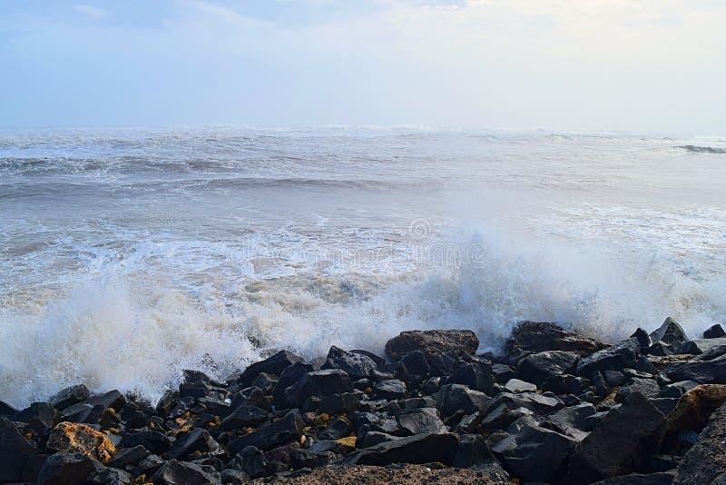 Garoa de água cai com impacto de onda marítima em rochas na costa com céu azul - fundo aquático natural do oceano fotografia de stock
