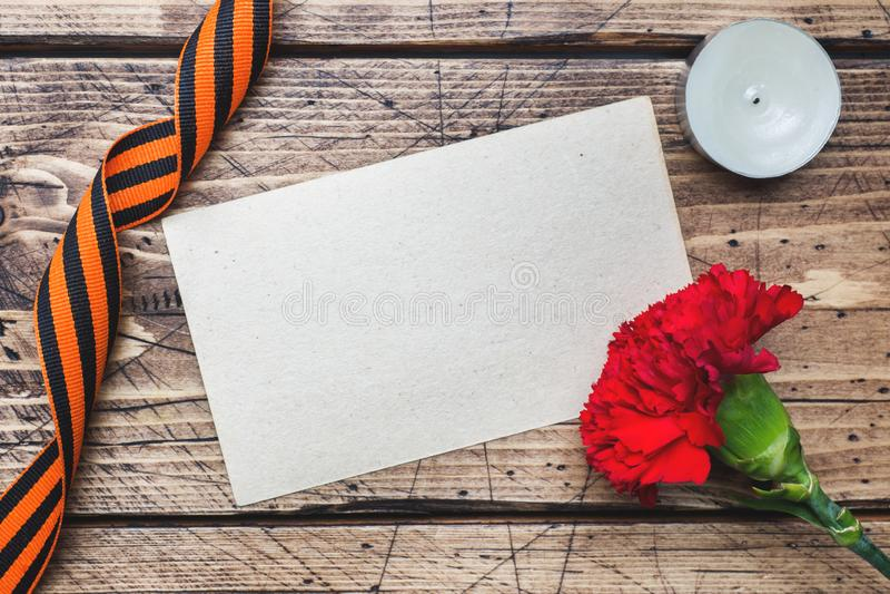 Garofani e nastro rossi di St George su fondo di legno Il simbolo pu? 9, il giorno di vittoria fotografia stock libera da diritti