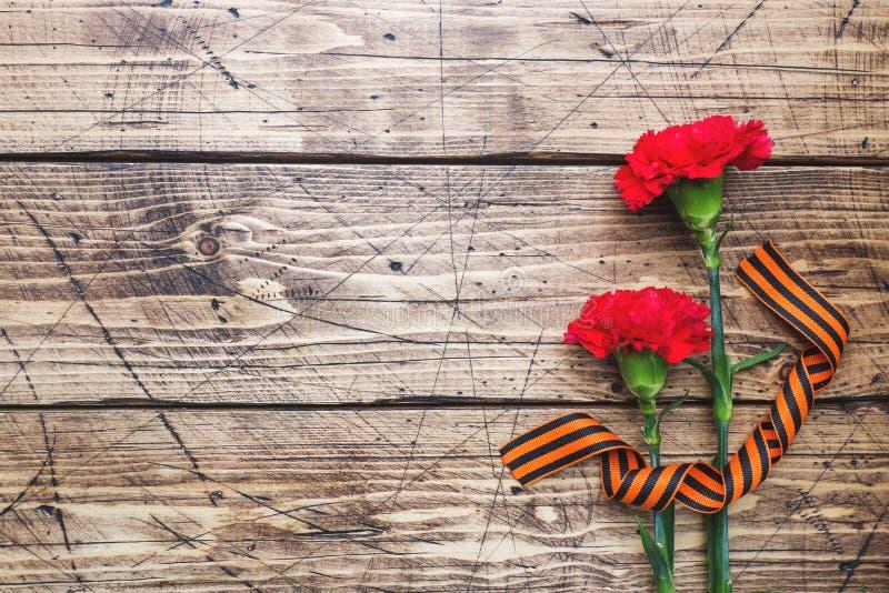 Garofani e nastro rossi di St George su fondo di legno Il simbolo pu? 9, spazio della copia del giorno di vittoria fotografia stock