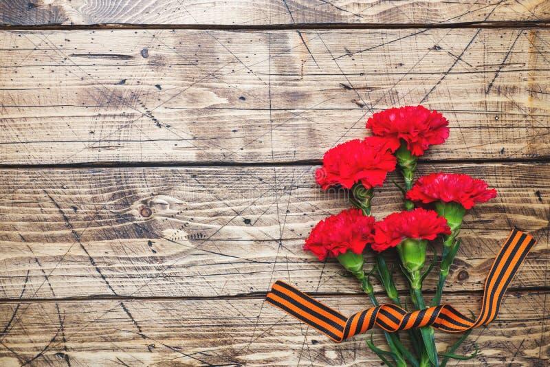 Garofani e nastro rossi di St George su fondo di legno Il simbolo pu? 9, spazio della copia del giorno di vittoria fotografia stock libera da diritti