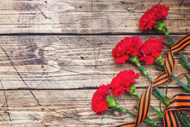 Garofani e nastro rossi di St George su fondo di legno Il simbolo pu? 9, spazio della copia del giorno di vittoria fotografie stock
