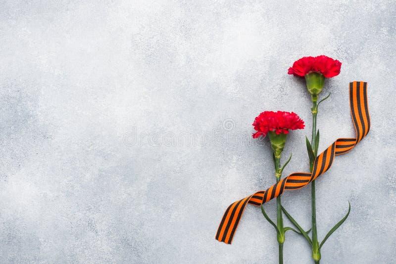 Garofani e nastro rossi di St George su un fondo concreto Il simbolo può 9, spazio della copia del giorno di vittoria fotografie stock libere da diritti