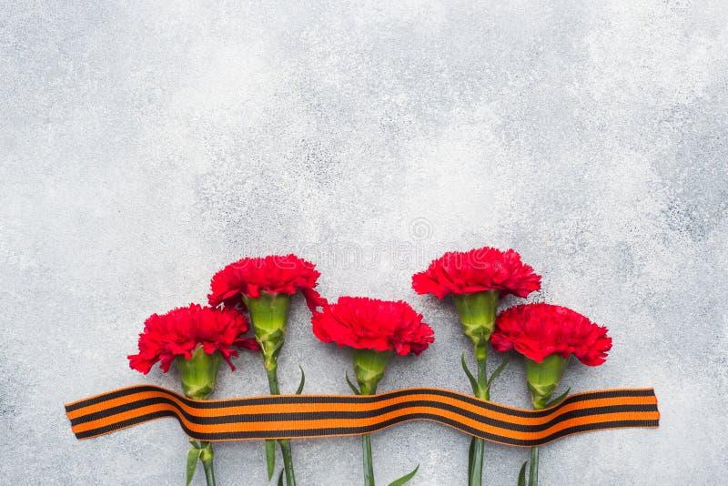 Garofani e nastro rossi di St George su un fondo concreto Il simbolo può 9, spazio della copia del giorno di vittoria fotografia stock