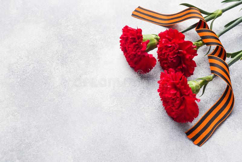 Garofani e nastro rossi di St George su un fondo concreto Il simbolo può 9, spazio della copia del giorno di vittoria fotografie stock