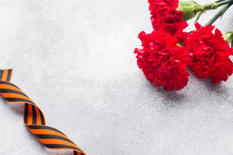 Garofani e nastro rossi di St George su un fondo concreto Il simbolo può 9, spazio della copia del giorno di vittoria immagine stock libera da diritti