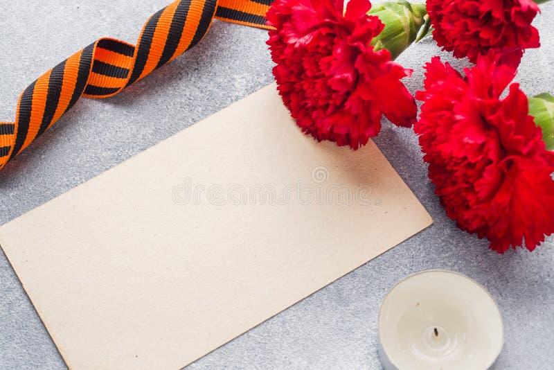 Garofani e nastro rossi di St George su un fondo concreto Il simbolo può 9, spazio della copia del giorno di vittoria immagine stock