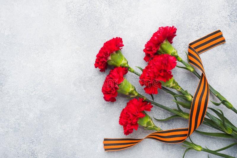 Garofani e nastro rossi di St George su un fondo concreto Il simbolo pu? 9, spazio della copia del giorno di vittoria immagine stock