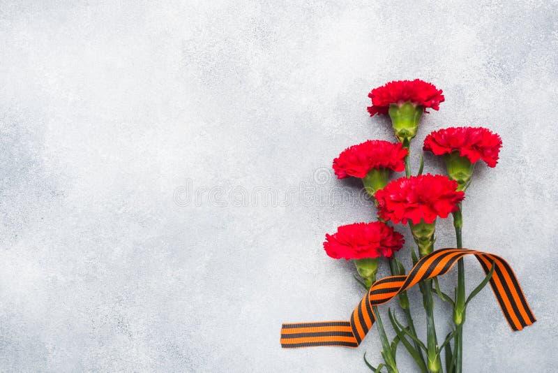 Garofani e nastro rossi di St George su un fondo concreto Il simbolo pu? 9, spazio della copia del giorno di vittoria fotografia stock libera da diritti