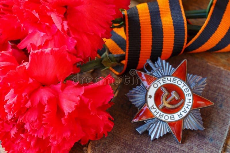 Garofani rossi con il nastro del ` s di St George e l'ordine del Soviet della guerra patriottica dell'iscrizione patriottica di g fotografie stock
