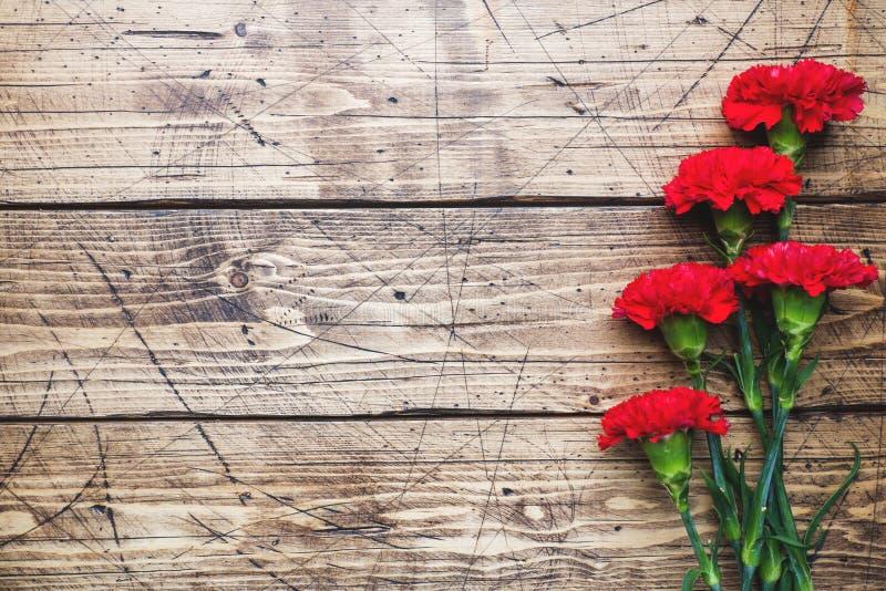 Garofani rossi su fondo di legno con lo spazio della copia Carta di festa della Mamma, San Valentino fotografie stock libere da diritti