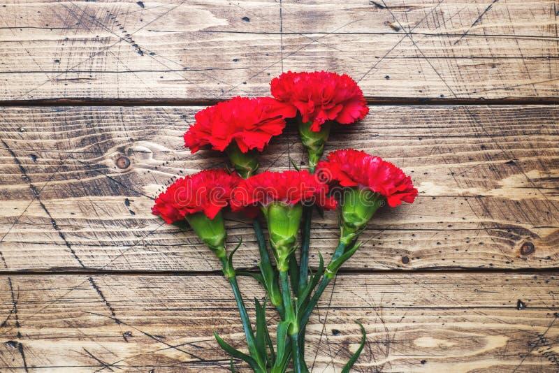 Garofani rossi su fondo di legno con lo spazio della copia Carta di festa della Mamma, San Valentino fotografie stock