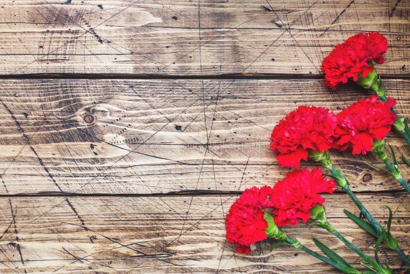 Garofani rossi su fondo di legno con lo spazio della copia Carta di festa della Mamma, San Valentino immagine stock