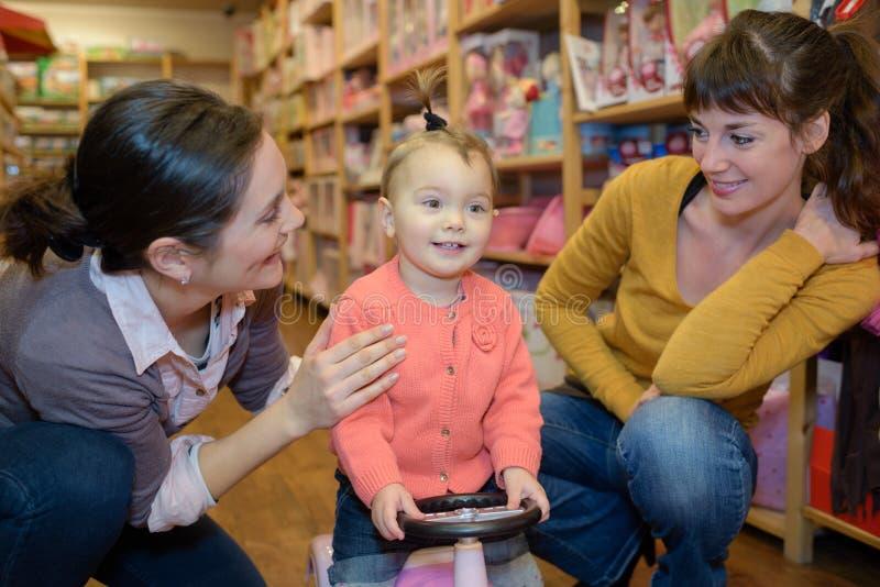 Garota adorável olha para brinquedos na loja de brinquedos fotografia de stock