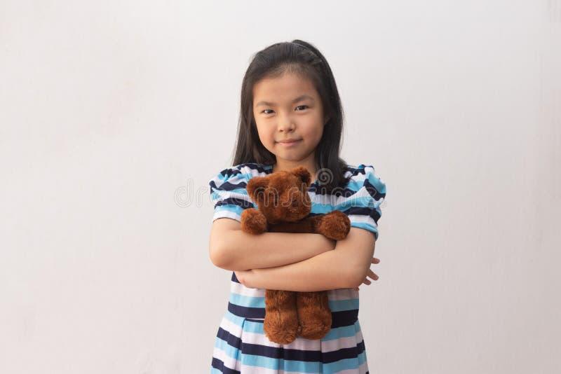 Garota asiática abraçando um ursinho fotografia de stock royalty free