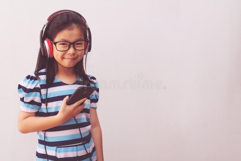 Garota asiática com fones de ouvido ouvindo música foto de stock