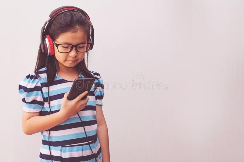 Garota asiática com fones de ouvido ouvindo música imagens de stock