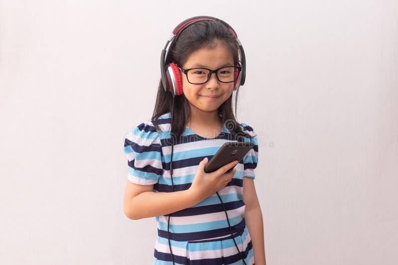 Garota asiática com fones de ouvido ouvindo música foto de stock royalty free