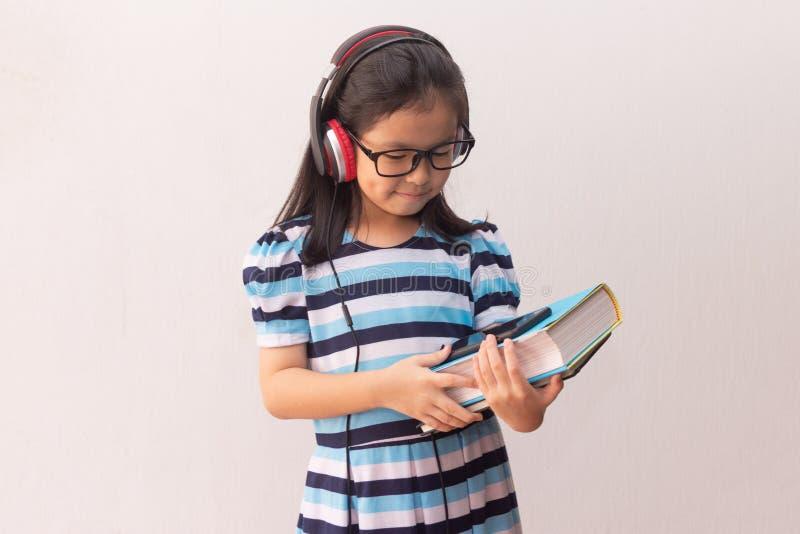 Garota asiática com fones de ouvido ouvindo música e segurando livros imagens de stock royalty free