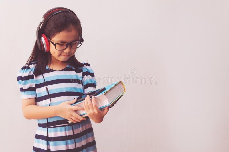 Garota asiática com fones de ouvido ouvindo música e segurando livros fotografia de stock