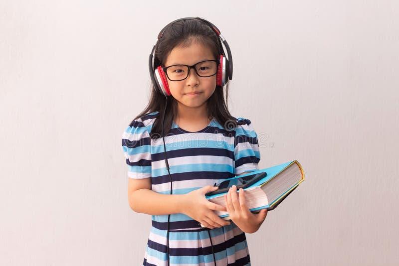 Garota asiática com fones de ouvido ouvindo música e segurando livros fotos de stock royalty free