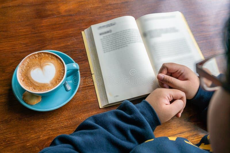 Garota asiática fica em casa e lê livro em quarentena em Coronavírus imagem de stock royalty free