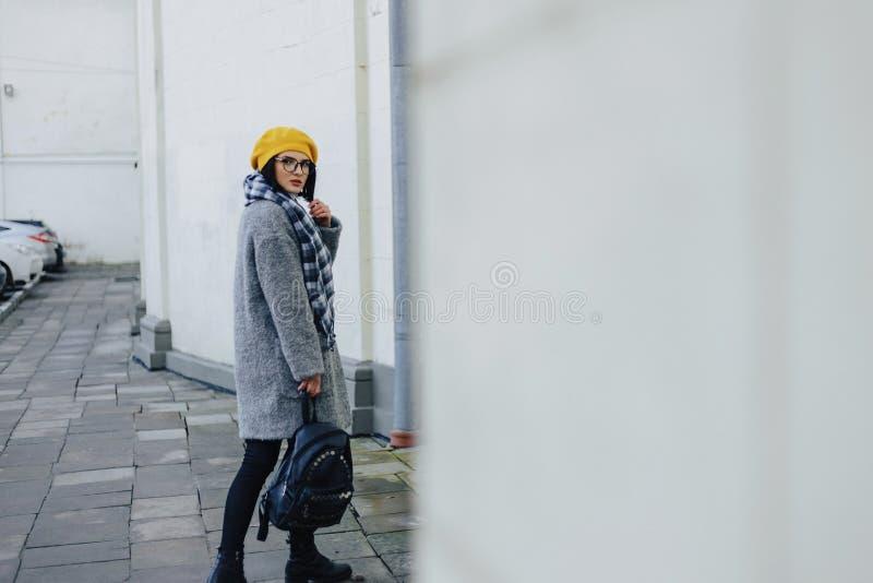 Garota atrativa de óculos de casaco e estilo livre de Beret amarelo andando fotografia de stock