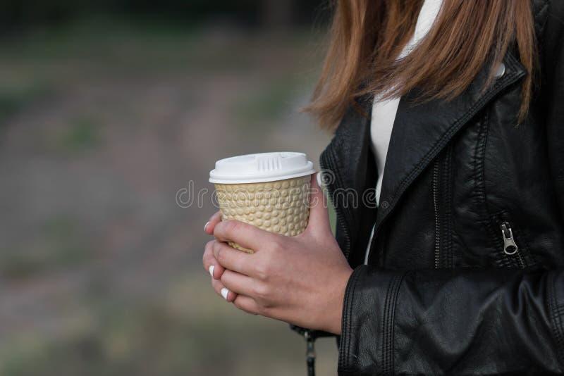 Garota com café na jaqueta de couro no outono ou floresta Foco seletivo e fundo de bolso mole borrado imagem de stock
