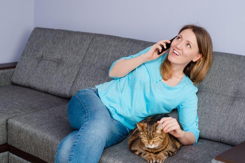 Garota com gato está no telefone foto de stock royalty free
