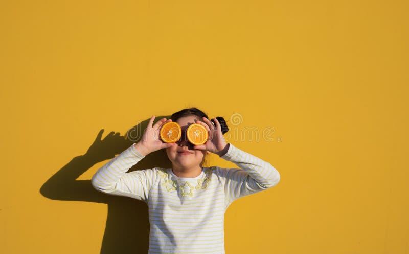 Garota com laranja no fundo amarelo fotos de stock