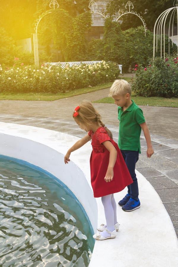 garota com pinos de cabelo em vestido vermelho e um garoto loiro em camiseta verde estão na fonte no parque fotos de stock