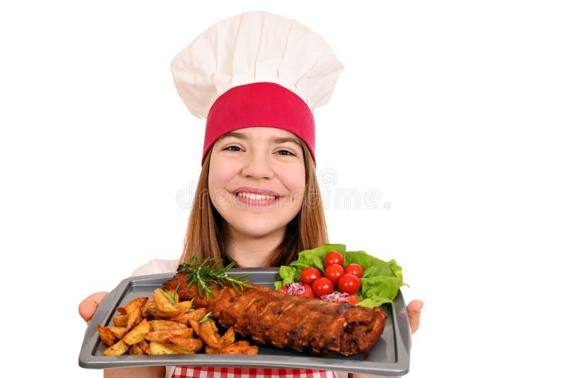 Garota cozinheira com costelas de porco em prato imagens de stock