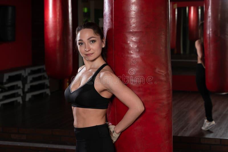 garota de caça sexy no ginásio com saco de boxe Modelo de cabeleireira de mulher longa descansando após boxe fotos de stock royalty free